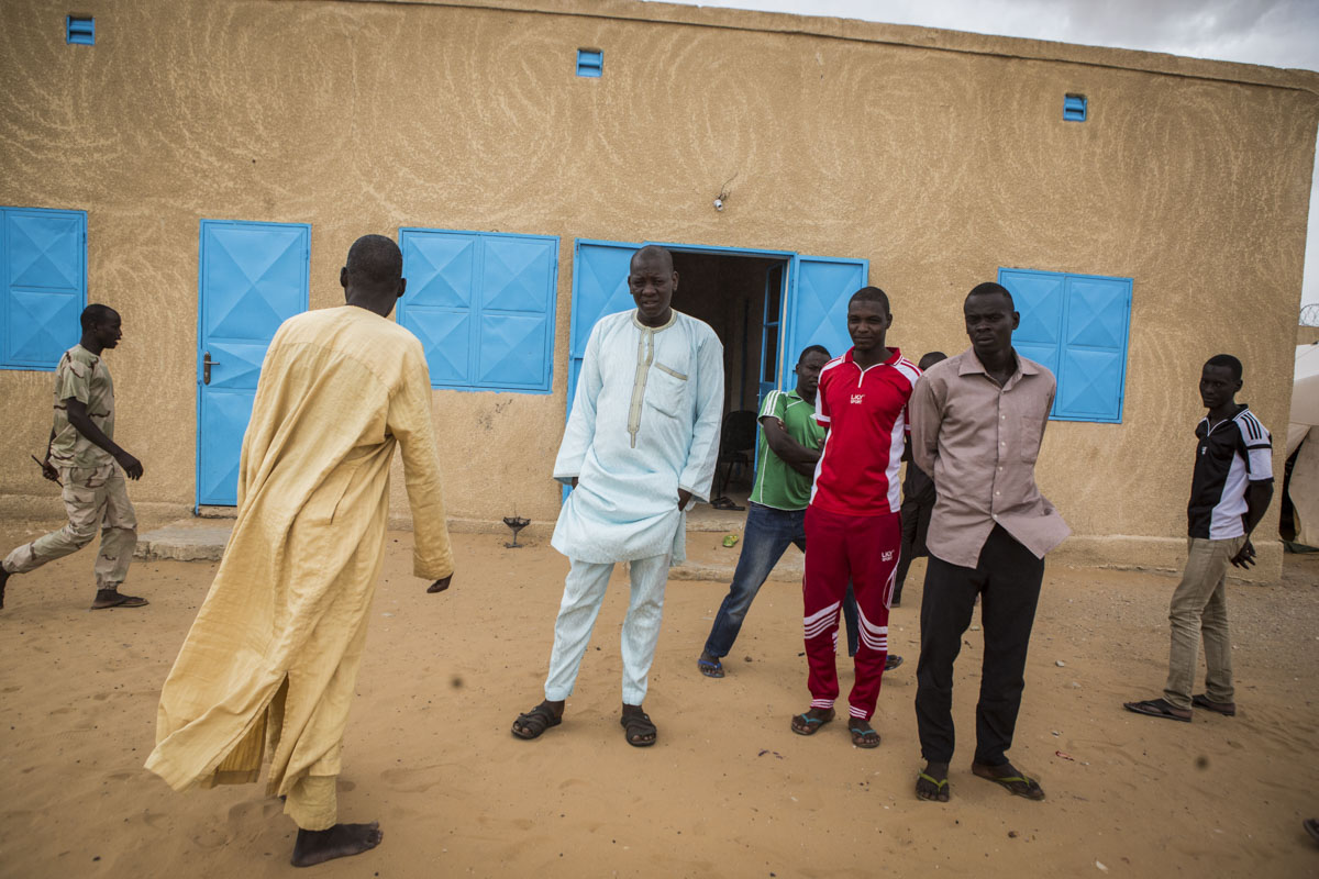 Mustafa, 27, (c) gathers with other men after prayers at an internment camp for ex-Boko Haram combatants in Goudoumaria, Niger, August 2018.