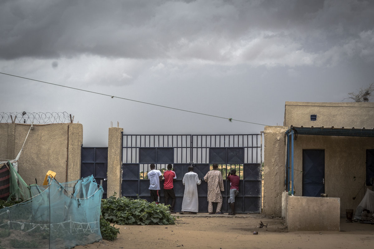 Men stand at the gate watching as others push a car free from the sand at an internment camp for ex-Boko Haram combatants in Goudoumaria, Niger, August 2018.