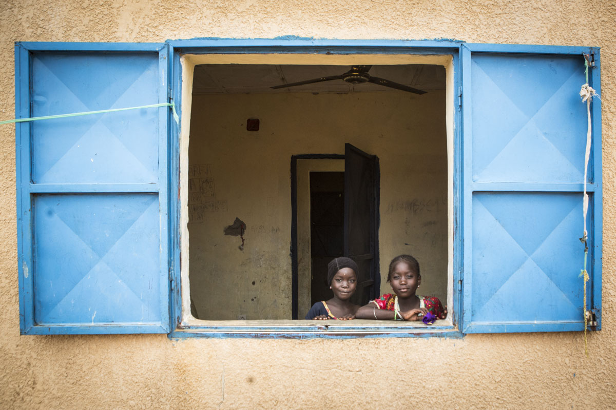 Luma, 6 (l) and Busam, 9, stand in the window of their room at an internment camp for ex-Boko Haram combatants and their families in Goudoumaria, Niger, August 2018.