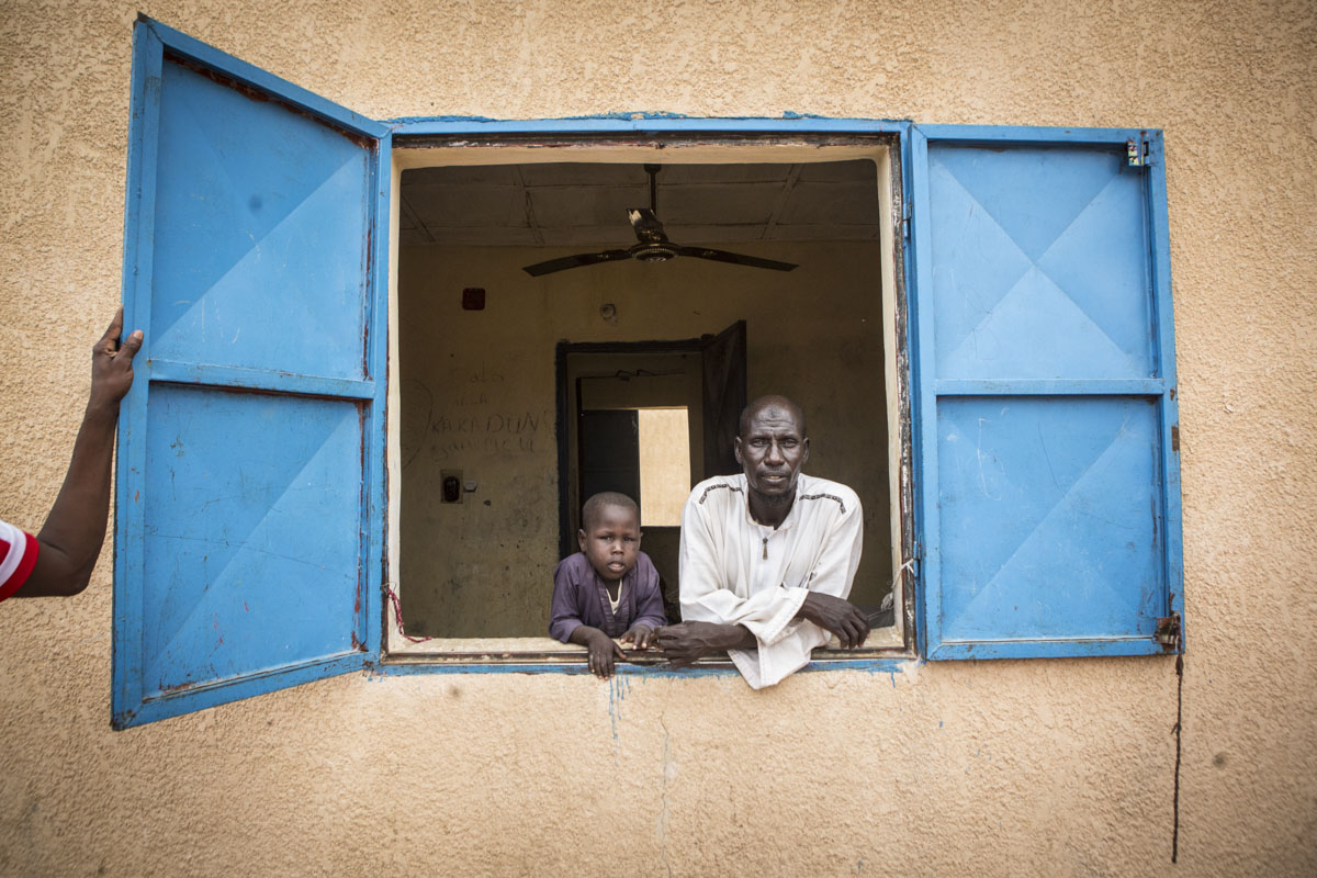 Abukhar, 45, and his son Abukhar, 6, look out the window of their dormitory room at an internment camp for ex-Boko Haram combatants in Goudoumaria, Niger, August 2018. Yassine and his family have been at the camp for 8 months.