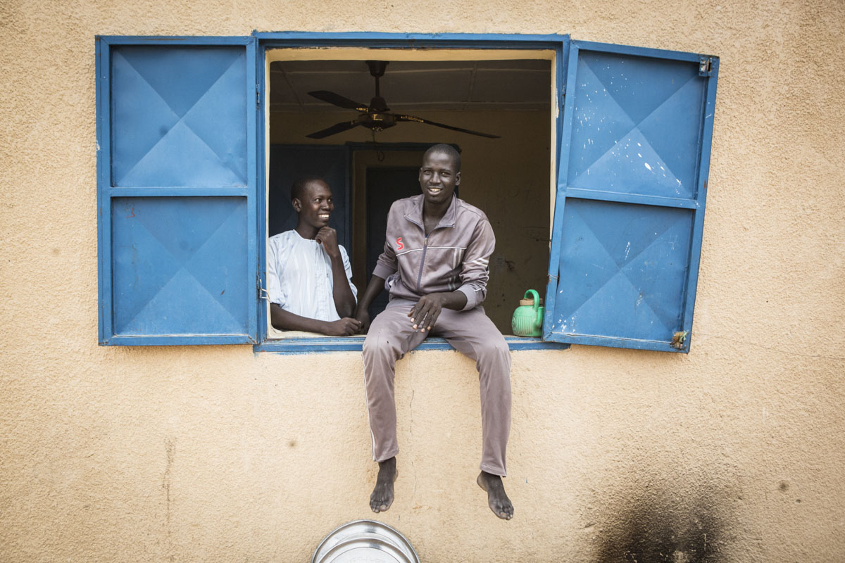 Mustafa, 20 (c) and Usman, 17, stand in the window of a dormitory room  at an internment camp for ex-Boko Haram combatants in Goudoumaria, Niger in August 2018.