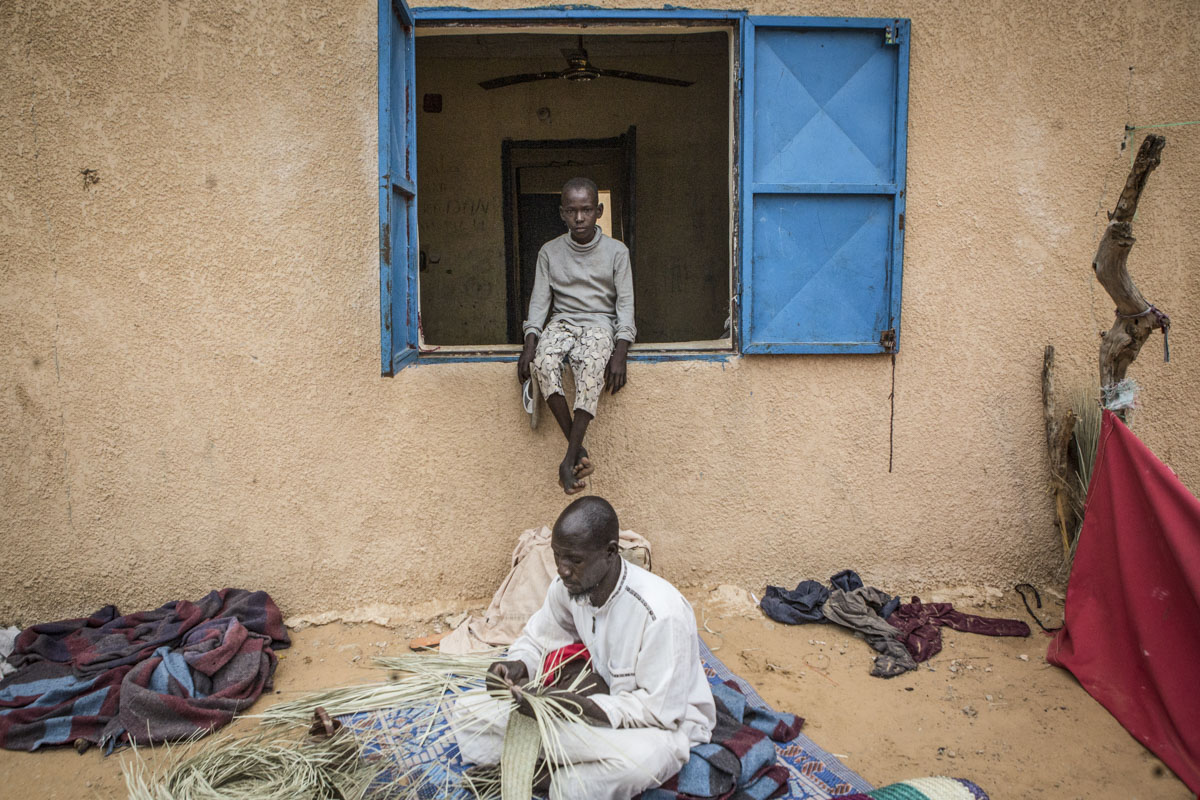 Ari,12, sits in the window as Abukar Bulama, 45 weaves a straw mat at an internment camp for ex-Boko Haram combatants in Goudoumaria, Niger August 2018.