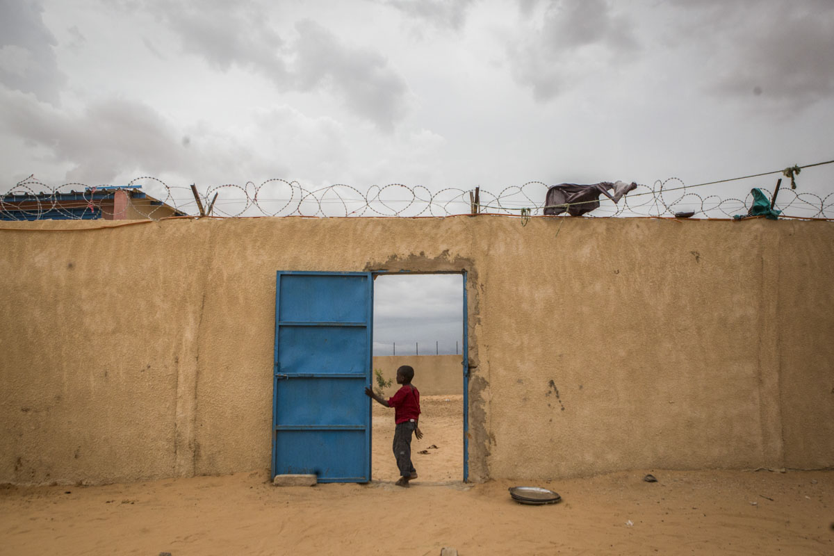 A boy stands in a doorway at an internment camp for ex-Boko Haram combatants in Goudoumaria, Niger, August 2018.