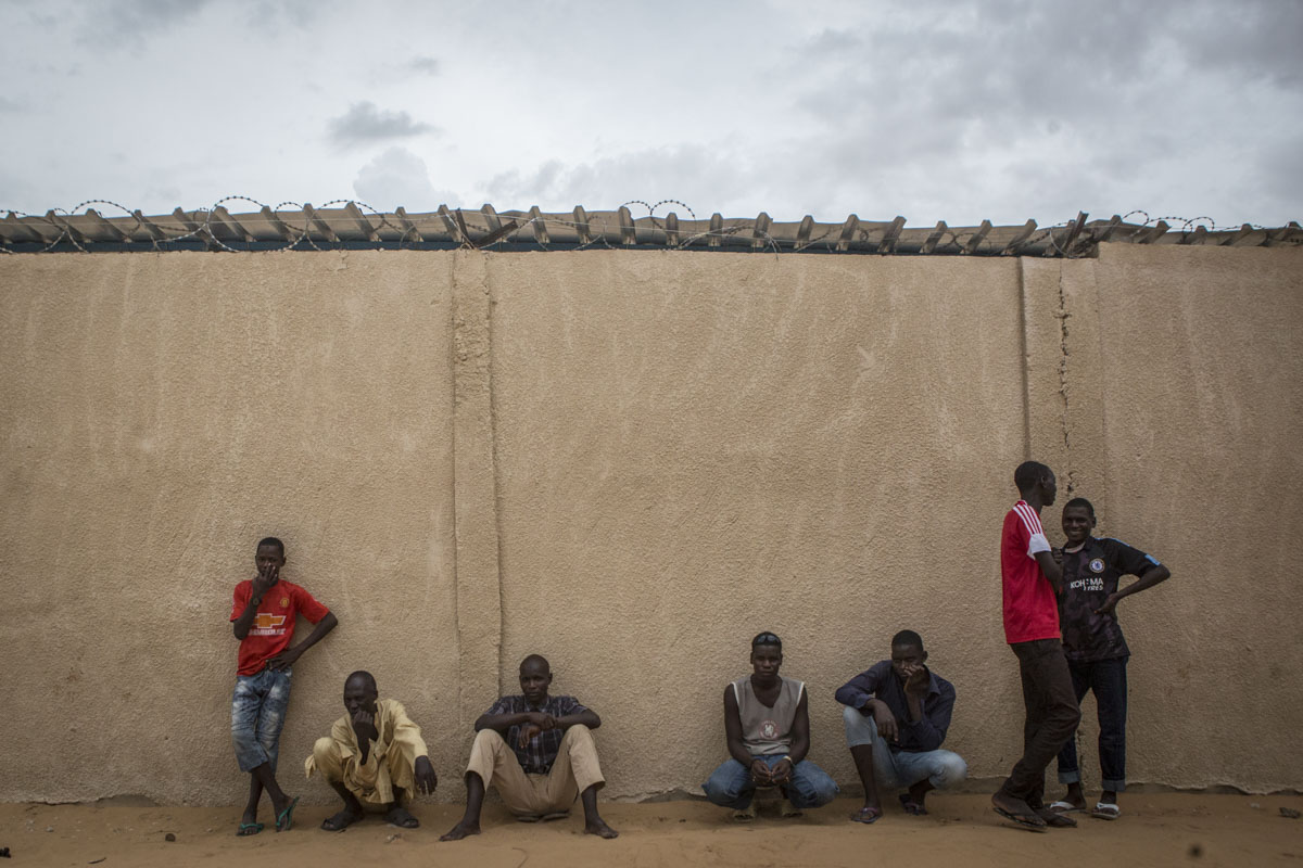 Men lean against a wall at an internment camp for ex-Boko Haram combatants in Goudoumaria, Niger, August 2018.