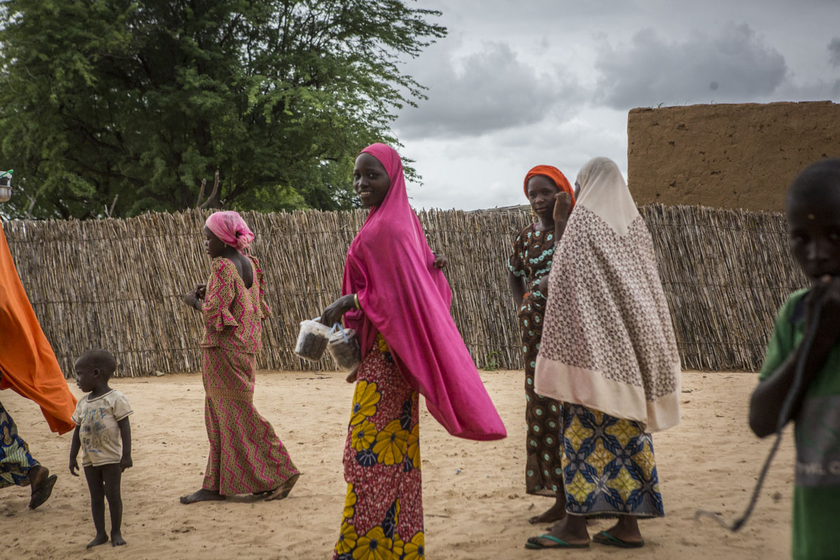 Women walk through Boudouri Internally Displaced persons camp outside of Diffa, Niger, September 2018.The original village of Boudouri housed between 200-300 people but now, because of the crisis, over 5000 take refuge with little to no aid for the last five months.