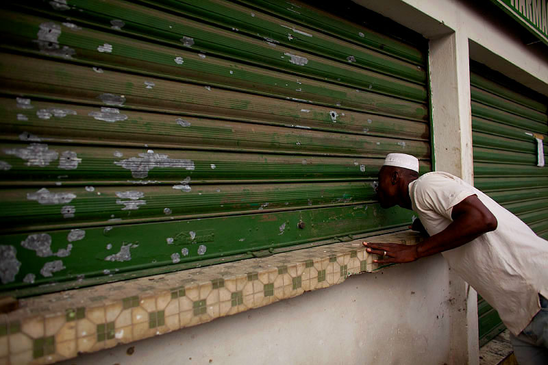 a man looks through a bullet hole in a security gate in abobo