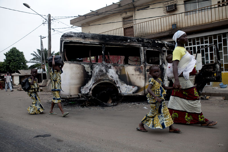 a woman walks with her children passed a burnt truck in abobo