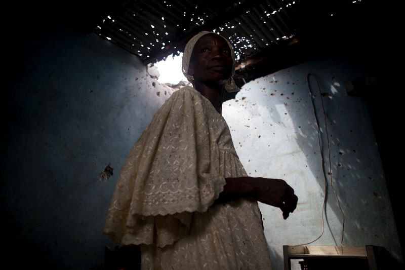 karidija cisse walks through her kitchen after it was hit by a mortar