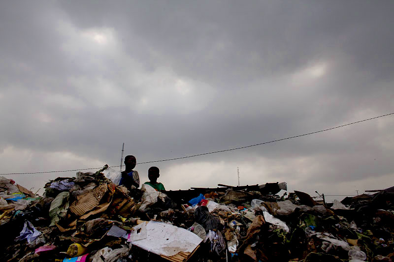 children stand at the top of one of many trash piles which have collected in abidjan. due to the crisis, cash has become so scarce in the world's largest cocoa producing country that laurent gbagbo is unable to pay his city employees in full