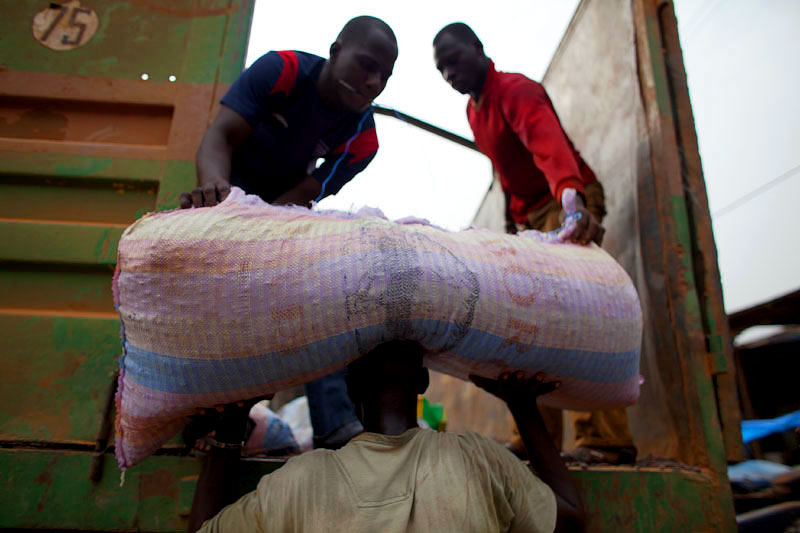 Men unload sacks of cocoa beans in San Pedro, Ivory Coast.  The San Pedro Port is the primary point for exporting raw materials, especially cocoa, out of the country. At times, cocoa sacks are emptied into vacuum containers as a method of transport overseas.