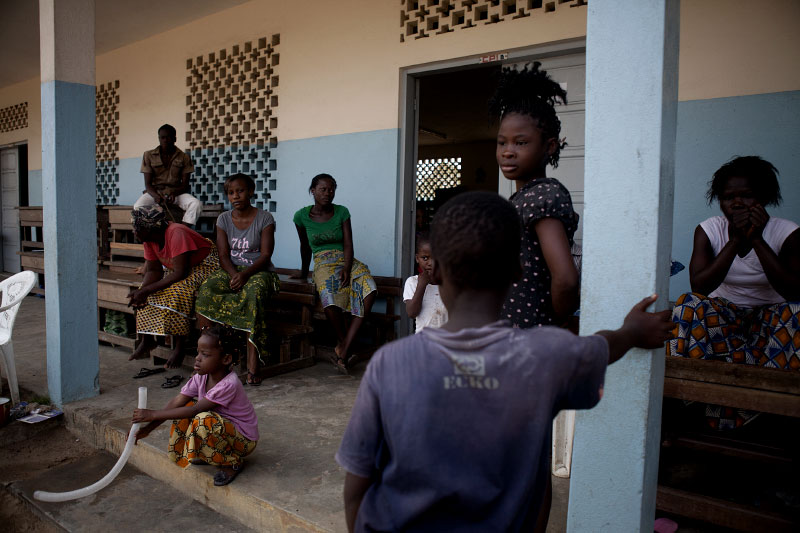 women and children gather at a catholic school being used as a shelter for refugees fleeing violence in abobo