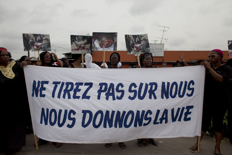 Women march through the streets mourning the deaths of the victims of the political violence, carrying a sign translating to {quote}Do not shoot us. We give life{quote} the morning of Tuesday, March 8, 2011 in Treichville, a suburb of Abidjan, Ivory Coast. This afternoon in Treichville, after finishing prayers (both Christian and Muslim) the marching women encountered the {quote}Compagnies Republicaines de Securité{quote} (CRS), special riot police loyal to Laurent Gbagbo. Its reported that the neighborhood youth guard stood in a line between the women and the CRS to protect the women when the CRS opened fire. At least four were killed including one woman and unknown number were injured..