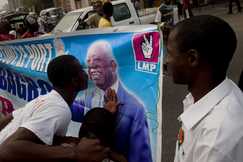 a man kisses a banner with an image of laurent gbagbo at a rally in abidjan