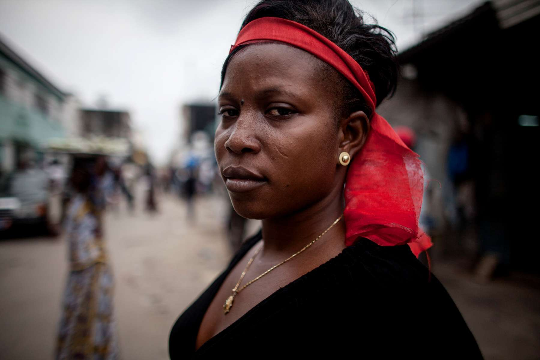 Abiba Ouattara, 25, waits for the start of the march mourning the deaths of the victims of the political violence on Tuesday, March 8, 2011 in Treichville, Ivory Coast. This afternoon in Treichville, after finishing prayers (both Christian and Muslim) the marching women encountered the {quote}Compagnies Republicaines de SecuritÈ{quote} (CRS), special riot police loyal to Laurent Gbagbo. Its reported that the neighborhood youth guard stood in a line between the women and the CRS to protect the women when the CRS opened fire. At least four were killed including one woman and unknown number were injured.