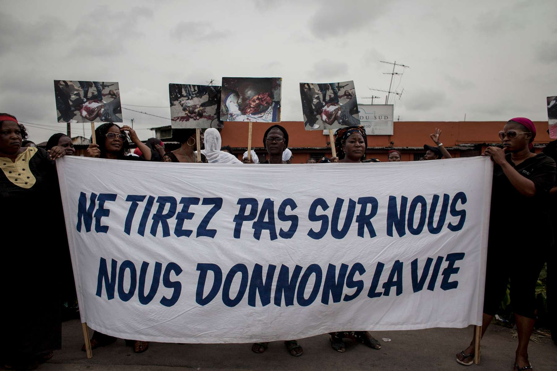 Women march through the streets mourning the deaths of the victims of the political violence, carrying a sign translating to {quote}Do not shoot us. We give life{quote} the morning of Tuesday, March 8, 2011 in Treichville, a suburb of Abidjan, Ivory Coast. This afternoon in Treichville, after finishing prayers (both Christian and Muslim) the marching women encountered the {quote}Compagnies Republicaines de SecuritÈ{quote} (CRS), special riot police loyal to Laurent Gbagbo. Its reported that the neighborhood youth guard stood in a line between the women and the CRS to protect the women when the CRS opened fire. At least four were killed including one woman and unknown number were injured.