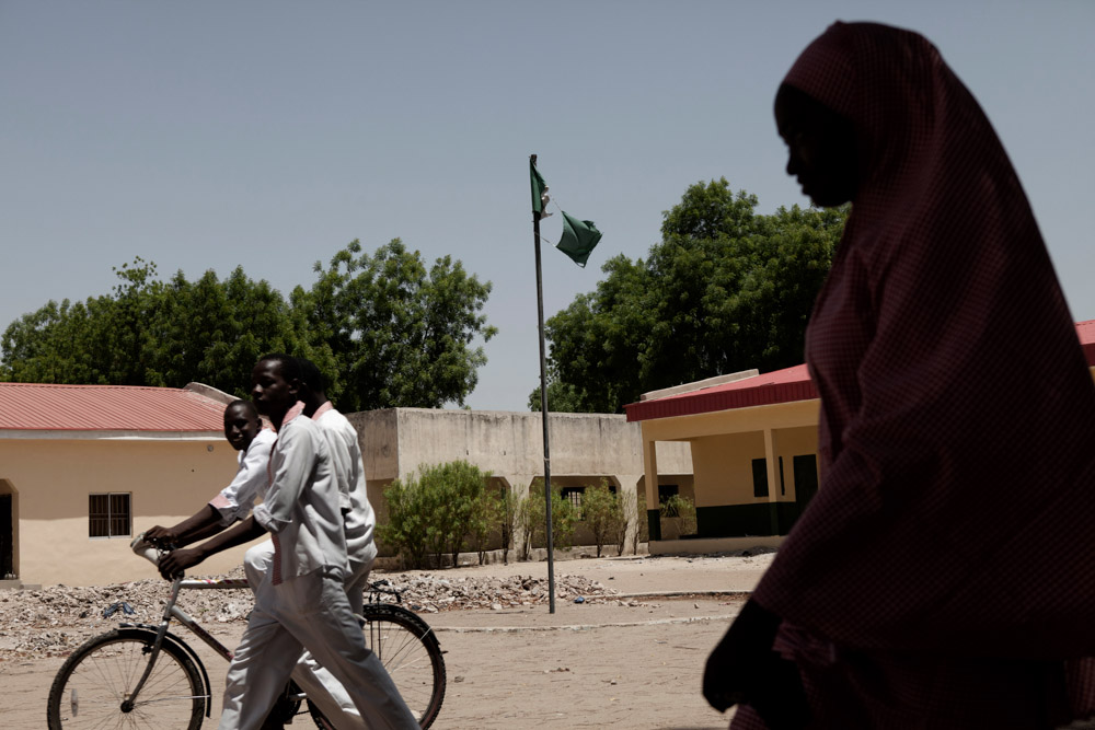 Students pass a tattered Nigerian flag at the Sanda Kyarimi Government Day Secondary School in Maiduguri, Nigeria in May 2013. After the Sanda Kyarimi School was attacked by Boko Haram in late March, many students and teachers have yet to return out of fear of another attack.