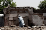 A man walks passed the remains of the Customs Market, a Boko Haram stronghold, after it was burned down by the Nigerian military's Joint Task Force (JTF) in Maiduguri, Nigeria. 2013