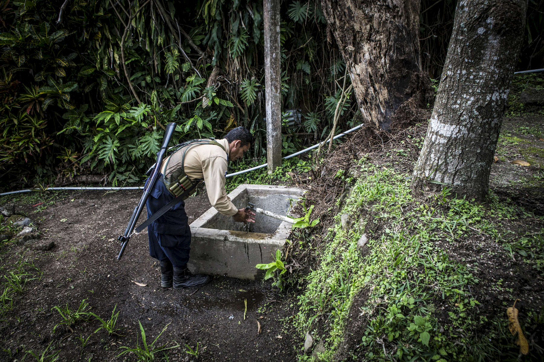 Nejapa, El Salvador- A security guard washes his hands at an outdoor tap at Miranda Cafe in Nejapa, El Salvador on Friday, June 22, 2018.Nejapa is not only home to a number of bottling plants including Coca Cola and Lactolac, it also lies above one of El Salvador's largest aquifers, feeding neighboring communities and much of San Salvador.The San Antonio River, once a main source of water for Nejapa, has been contaminated by the waste produced by industrial bottling plants since their arrival in 1996. Bio filtration systems were installed but have been broken since 2006. (Jane Hahn)