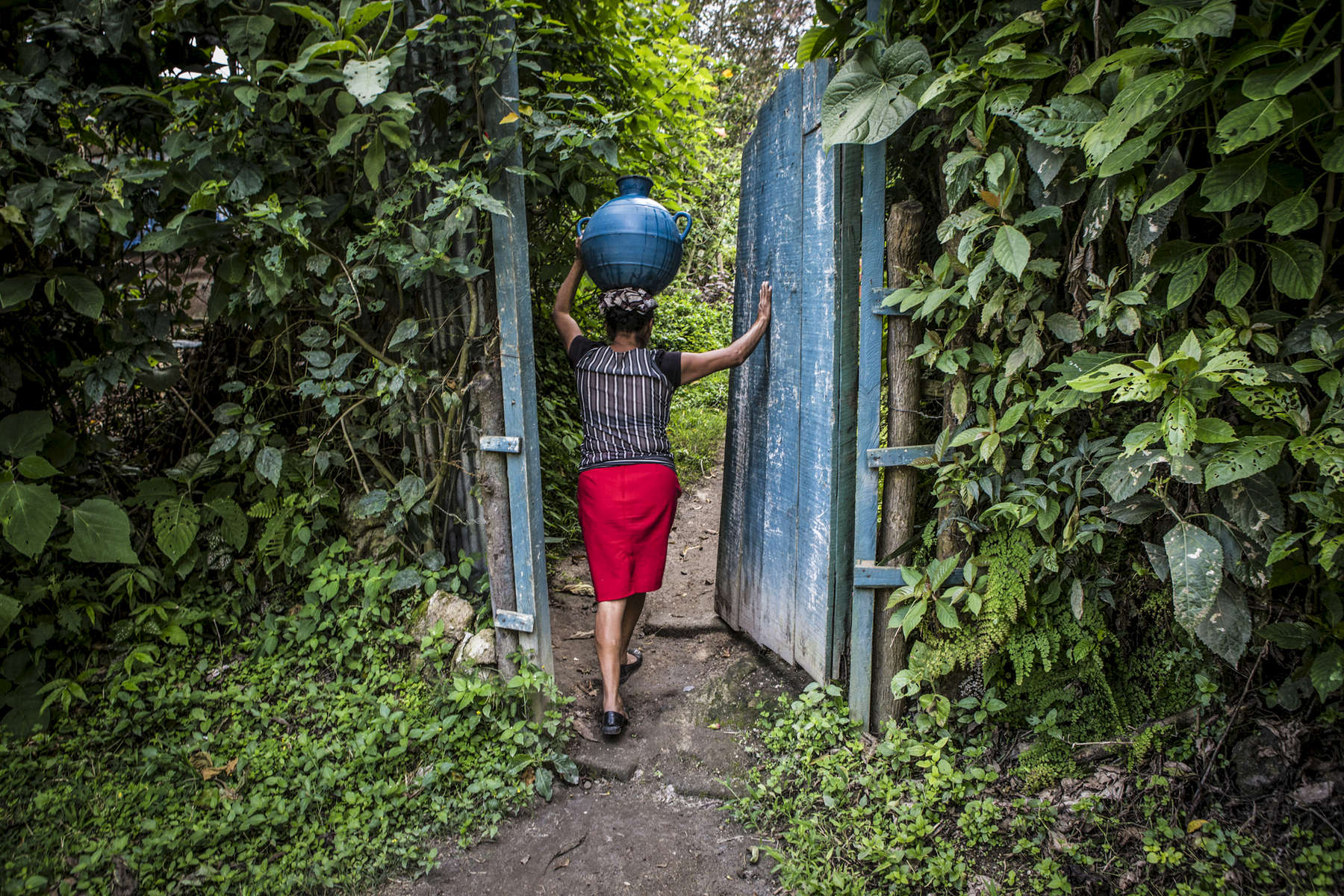 Nejapa, El Salvador- Zoila Ramirez, 40, carries a jug of water to her home in San Jeronimo Los Planes, Nejapa, El Salvador June 2018. Water is collected during the rainy season in the communal tank and sold for 10 cents a jug during the dry season, money raised is used to fund water trucks once the tank runs dry (usually the tank only lasts for two months into the dry season). Unfortunately the roof was lost during a recent hurricane and very little water has been collected since, worrying the Perez family. Nejapa is not only home to a number of bottling plants including Coca Cola and Lactolac, it also lies above one of El Salvador's largest aquifers, feeding neighboring communities and much of San Salvador.The San Antonio River, once a main source of water for Nejapa, has been contaminated by the waste produced by industrial bottling plants since their arrival in 1996. Bio filtration systems were installed but have been broken since 2006.  (Jane Hahn)