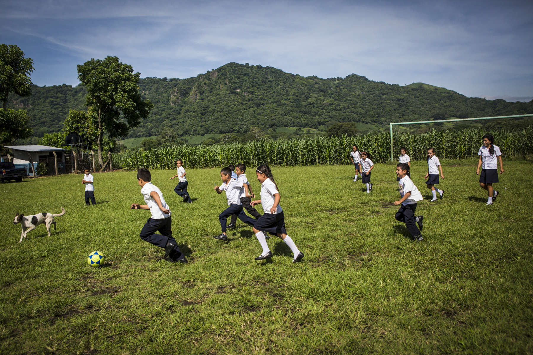 San Julian, El Salvador- Children play on the soccer field outside the Central School in San Julian, El Salvador on Tuesday, June 26, 2018. After many children and faculty grew ill from pesticides sprayed by plane onto the sugar cane field next to the school, the neighboring processing plant was ordered to spray by hand. Sugar cane processing plants must recycle the water they use in order to maintain environmental guidelines but according to local activists, the processing plant in San Julian pumps water directly from the river during the dry/harvesting season affecting the source and impacting their well water. (Jane Hahn)