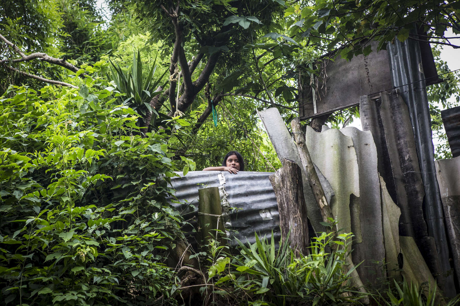 San Salvador, El Salvador- Marcella looks over the make shift wall outside her home in the San Antonio neighborhood where 28 houses (70 people) love without water,of San Salvador, El Salvador on Thursday, June 21, 2018. (Jane Hahn)