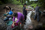 Cabañas, El Salvador- Maria Alejandrino, 34, (c) Teresa Serrano, 42, (l) a small community in Cabañas, El Salvador June 2018. Alejandrino and Serrano, like most people in their community of 112 families, has no access to running water and must come to the local well as early as 2am during the dry season for water. Even though politicians make promises during election season, the community has yet to see any change in their situation. Many have built make shift plumbing systems between homes to distribute water but most use rain water and community wells.(Jane Hahn)