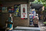 Nejapa, El Salvador- A woman carries a bench at an outdoor cafe decorated with advertisements for Coca Cola and other local sodas in Nejapa, El Salvador June 2018. Nejapa is not only home to a number of bottling plants including Coca Cola and Lactolac, it also lies above one of El Salvador's largest aquifers, feeding neighboring communities and much of San Salvador.The San Antonio River, once a main source of water for Nejapa, has been contaminated by the waste produced by industrial bottling plants since their arrival in 1996. Bio filtration systems were installed but have been broken since 2006. (Jane Hahn)