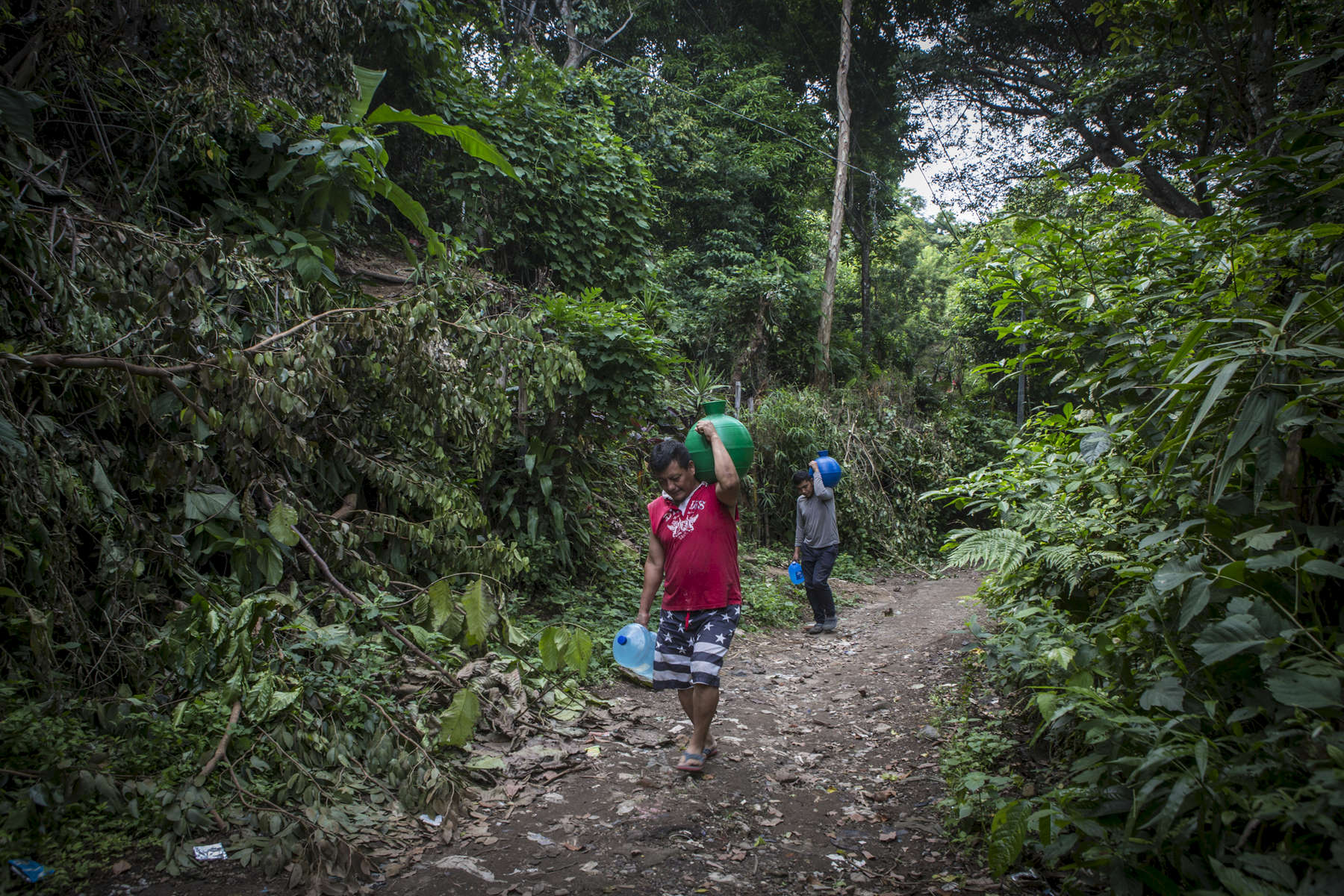 San Salvador, El Salvador- Carlos Melara, 45, carries jugs of water to his home in the San Antonio neighborhood where 28 houses (70 people) live without water,of San Salvador, El Salvador June 2018. During the dry season, Melara makes 12 trips to the communal water tap and four in the rainy season when they collect rain water to use for cleaning and bathing. (Jane Hahn)