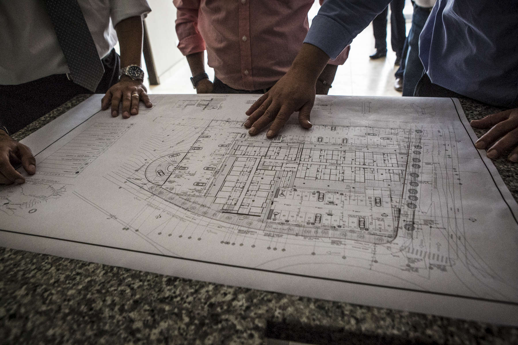 San Salvador, El Salvador- General Manager of Grupo Roble, Rafael Menéndez, Vice President of El Salvador, Óscar Ortiz, and President of ANDA (National Administration of Aqueducts and Sewers), Felipe Rivas look over blueprints to the Vista Tower construction site in San Salvador, El Salvador June 2018. (Jane Hahn)