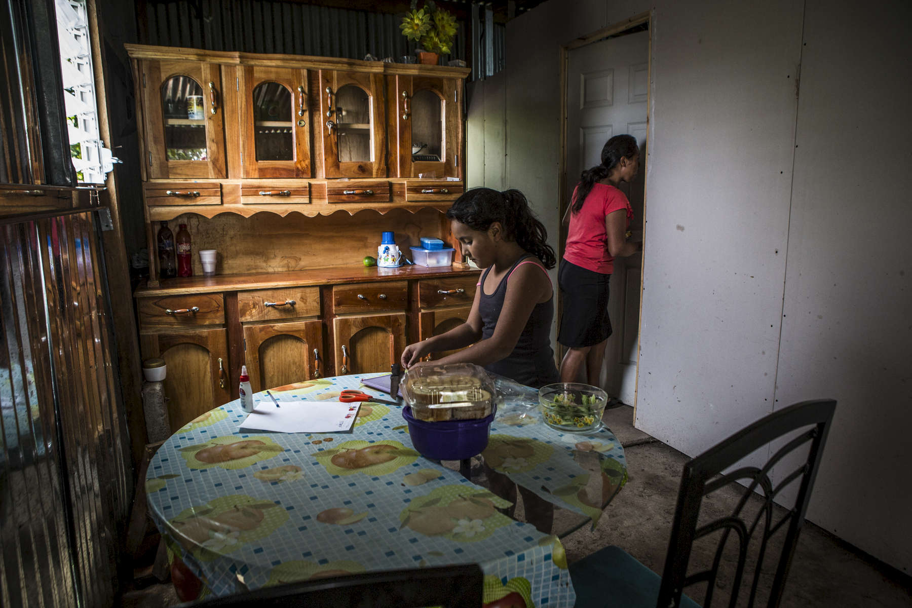 Nejapa, El Salvador- Priscilla Perez, 32, with her niece Aixa Ortiz, 9, make lunch at their home in San Jeronimo Los Planes, Nejapa, El Salvador June 2018. Water is collected during the rainy season in the communal tank and sold for 10 cents a jug during the dry season, money raised is used to fund water trucks once the tank runs dry (usually the tank only lasts for two months into the dry season). Unfortunately the roof was lost during a recent hurricane and very little water has been collected since, worrying the Perez family. Nejapa is not only home to a number of bottling plants including Coca Cola and Lactolac, it also lies above one of El Salvador's largest aquifers, feeding neighboring communities and much of San Salvador.The San Antonio River, once a main source of water for Nejapa, has been contaminated by the waste produced by industrial bottling plants since their arrival in 1996. Bio filtration systems were installed but have been broken since 2006. (Jane Hahn)