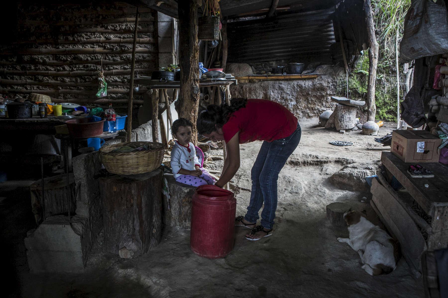 San Salvador, El Salvador- Ana Lillian Ramirez, 25, dresses her daughter Abigail Arias, 3,  in the San Antonio neighborhood where 28 houses (70 people) love without water of San Salvador, El Salvador June 2018. (Jane Hahn)