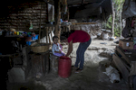San Salvador, El Salvador- Ana Lillian Ramirez, 25, dresses her daughter Abigail Arias, 3,  in the San Antonio neighborhood where 28 houses (70 people) love without water of San Salvador, El Salvador on Thursday, June 21, 2018. (Jane Hahn)