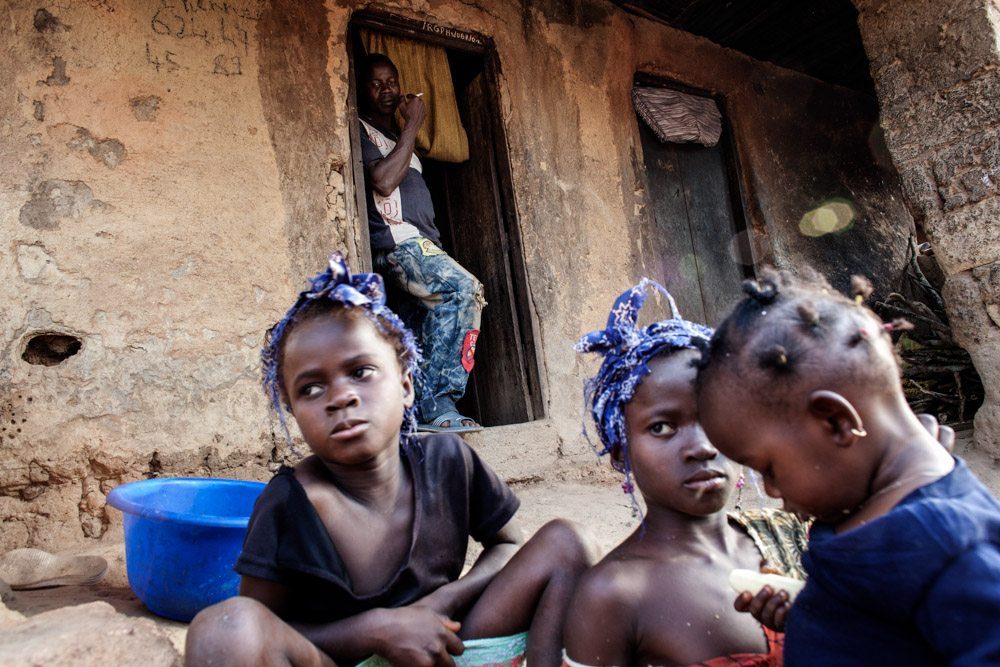 Etienne Ouamouno, 31, watches his daughters Marie, 6, Seyou, 7, and Kane, 2, (L to R) outside their home in Meliandou, Guinea on January 25, 2015. Meliandou is starting point of the Ebola epidemic when toddler Emile Ouamouno was the first to die from the virus in December of 2013. Since then 15 people have died of Ebola in the small village leading 200 people to flee since the start of the epidemic leaving 400 people. What was once a prosperous farming community, most now live in hunger unable to tend to their fields of mainly corn, palm and coffee.
