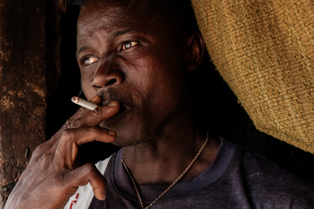 Etienne Ouamouno, 31, smokes a cigarette outside his home in Meliandou, Guinea