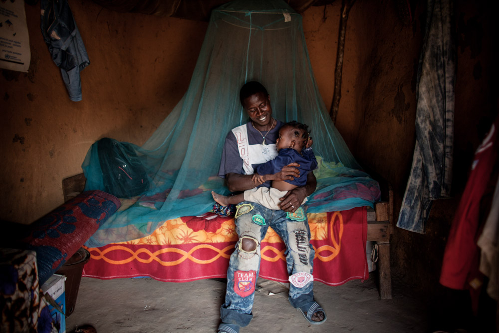 Etienne Ouamouno, 31, with his daughter Kane, 2, in their home in Meliandou, Guinea on January 25, 2015. Meliandou is starting point of the Ebola epidemic when toddler Emile Ouamouno was the first to die from the virus in December of 2013. Since then 15 people have died of Ebola in the small village leading 200 people to flee since the start of the epidemic leaving 400 people. What was once a prosperous farming community, most now live in hunger unable to tend to their fields of mainly corn, palm and coffee.