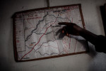 Cécé Kpoghomore, 45, director of the school, points to a map made by a student in his office in Meliandou, Guinea on January 25. 2015.
