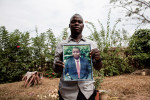 Jacques Mamy, 34, holds a photo of his father Reverend Moises Mamy outside of their home in N'zao, Guinea on January 23, 2015. Reverend Moises Mamy was one of eight people killed on September 16, 2014 while visiting the town of Womey in an attempt to educate people about Ebola.