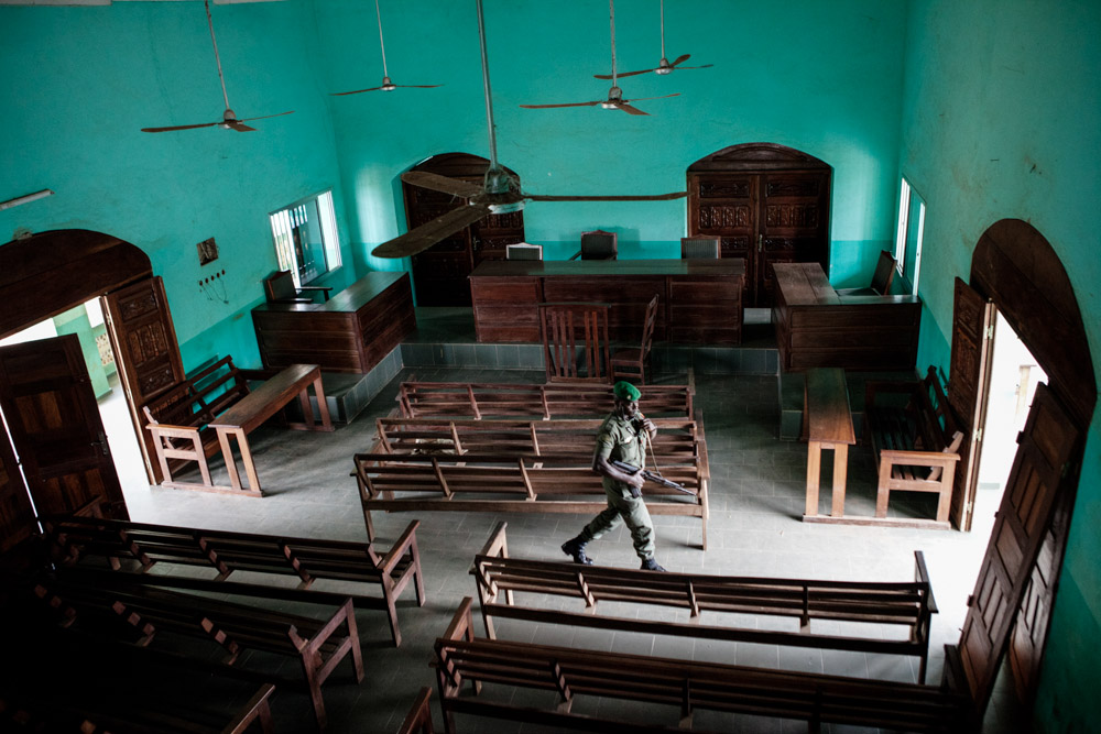 A solider walks through the main court room in Nzérékore, Guinea on January 23, 2015. This will most likely be the courtroom used to try the 34 people who are currently being held by authorities for the killing of eight people who traveled to Womey, Guinea to educate people about Ebola on September 16, 2014.