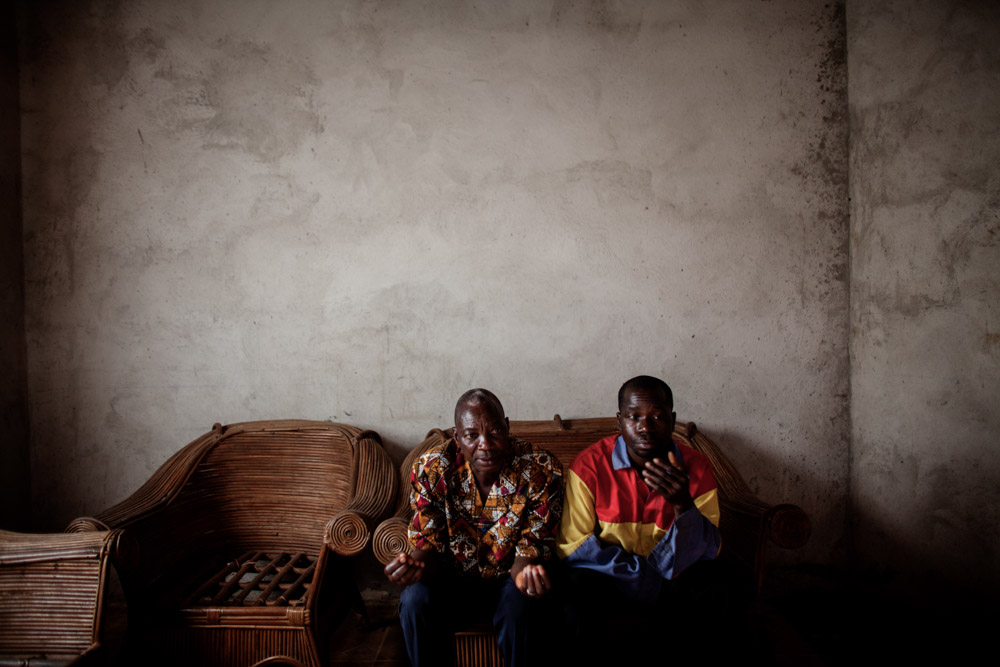 Vövpö Delamou, 67, village elder and Pepe Haba, 39, sits in the Haba home in Womey, Guinea on January 24, 2015. Delamou and Haba recouns the events September 16, 2014 when a government led group visiting Womey was attacked and eight people were killed while trying to educate people about Ebola. The people of Womey claim the military looted all of their belongings while their town was occupied.