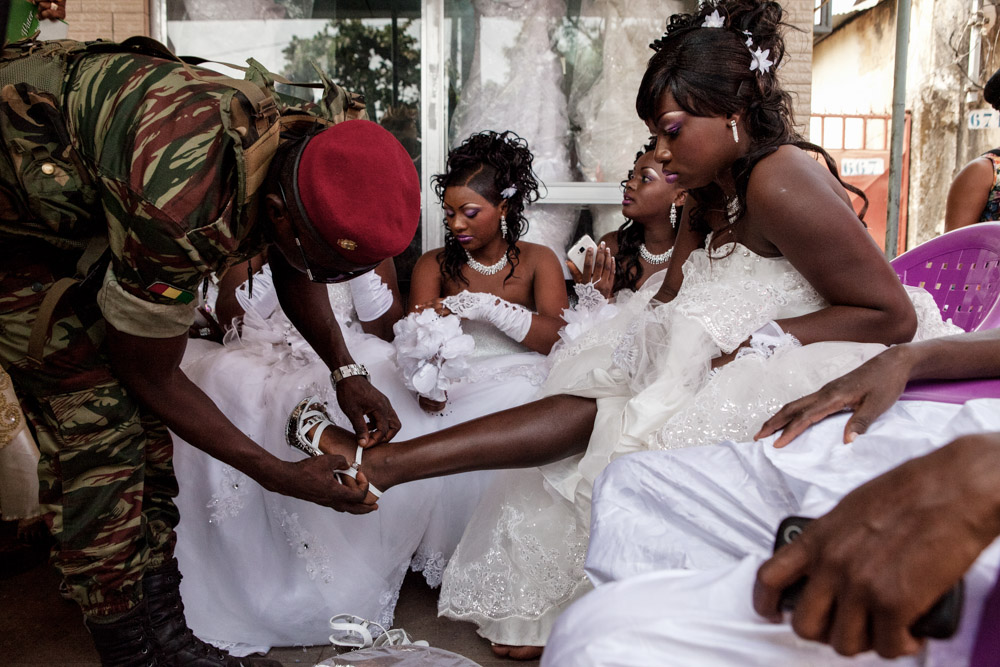 A member of the presidential guard helps his younger sister with her shoe, as other brides look on, just before her wedding outside of a hair salon in Conakry, Guinea