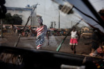 Girls walk passed a car being washed in Conakry, Guinea