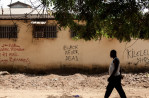 A man walks passed graffiti that reads {quote}Black Never Dead{quote} in Conakry, Guinea on January 27, 2015.