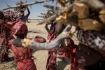 Girls, originally from Nigeria, carry remaining branches and shrubbery from trees that have been cut by other refugees outside of Guam Guam Camp in Diffa, Niger.Garin Wanzam Camp is the largest camp in the region hosting almost 23,000 displaced people. Many cut down trees in the area in order to help reduce the cost of firewood which can cost up to 30-40 percent of a family's monthly budget.