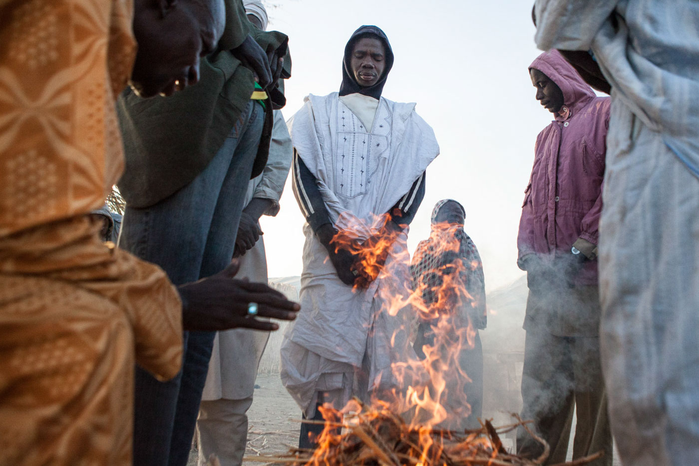 Men warm themselves by the fire in Djalori Camp in Diffa, Niger.300,000 people displaced by the Boko Haram crisis are taking refuge in southern Niger, straining the already vulnerable environment of the Lake Chad Basin.