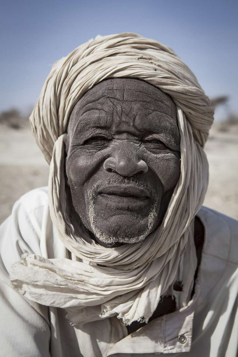 Mohammed Mboudou, digs for natron in Mayala, Chad February 2017. Mboudou has been mining for natron, a sodium based mineral found in pockets of areas around the basin, since he was 20 years old. As the water levels of the lake decrease, fields of natron are uncovered overtime. They are mined and sold to markets around the basin with Nigeria being the largest market. Since late 2014, the route to Nigeria has been cut off due to insecurity severely affecting the local market and incomes of the fishermen, farmers and miners and their ability to provide for their families.
