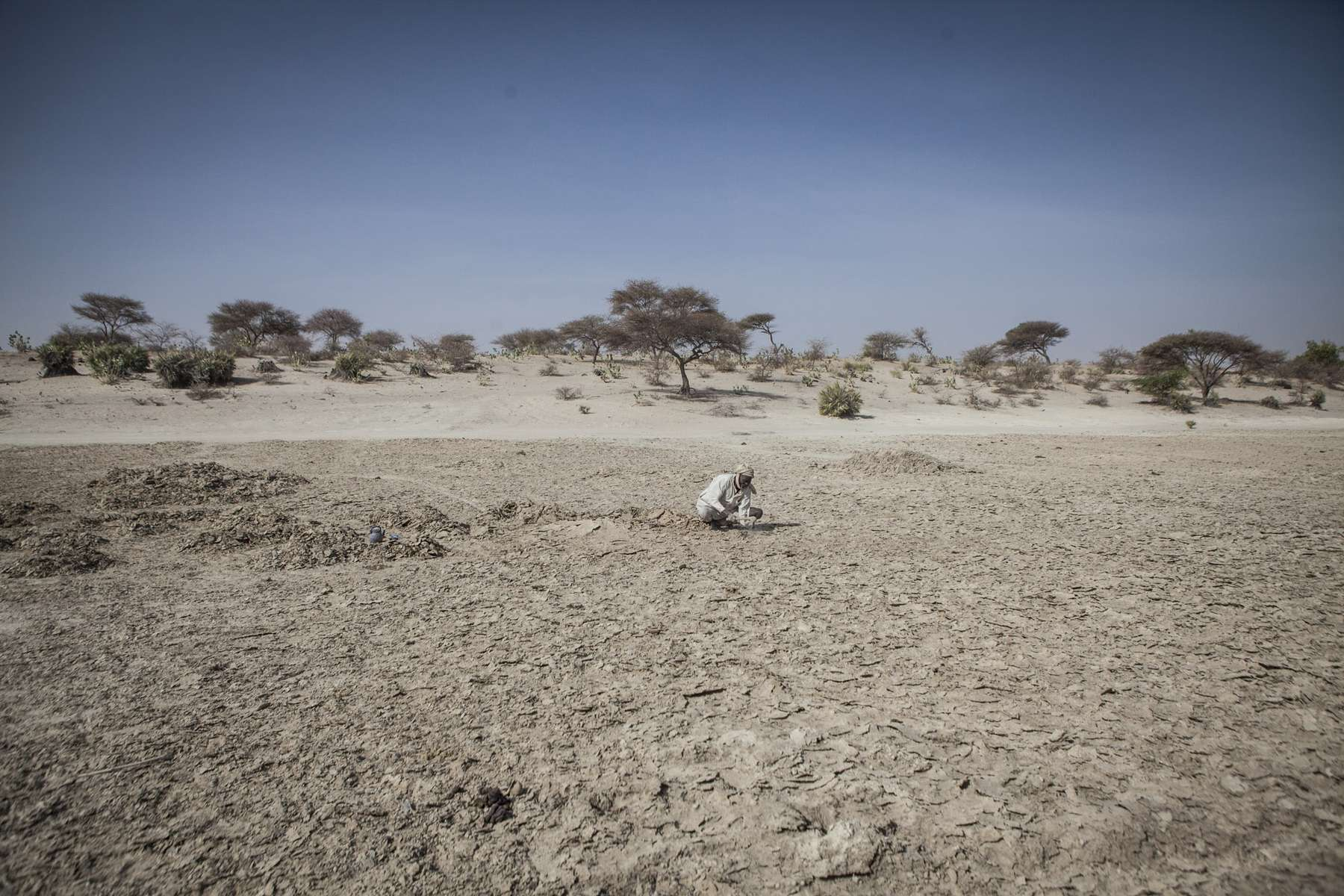 Mohammed Mboudou, digs for natron in Mayala, Chad on February 16, 2017. Mboudou has been mining for natron, a sodium based mineral found in pockets of areas around the basin, since he was 20 years old. As the water levels of the lake decrease, fields of natron are uncovered overtime. They are mined and sold to markets around the basin with Nigeria being the largest market. Since late 2014, the route to Nigeria has been cut off due to insecurity severely affecting the local market and incomes of the fishermen, farmers and miners and their ability to provide for their families.