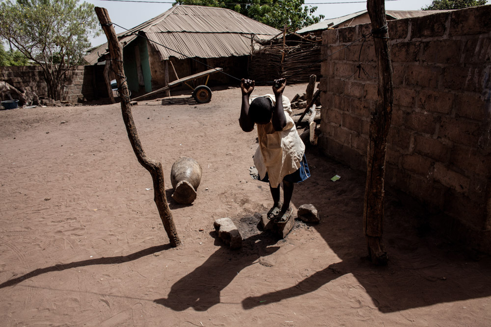 Ibrahima, 12, plays on a clothes line in Dampha Kunda Village