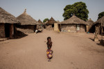 A young girls walks through the family compound of Fissa, 33, in Perai Village