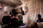 Susso, 38, plays with his children, niece and nephew in his home in Dampha Kunda Village. Susso, 38, has saved 17,000 Dalasis (roughly $400) in a lock box and plans to use a portion to fund the {quote}back way{quote} trip he will begin from the Gambia to Libya in close to a week and the rest he will leave for his family. This will be Susso's third attempt to reach Europe.