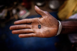 Susso, 38, holds the micro SD card he will use to store the photos he will take on the {quote}back way{quote} journey  to Europe (through the Gambia, Senegal, Mali, Burkina Faso, Niger through the desert to Libya), in his home in Dampha Kunda Village. This will be Susso's third attempt to reach Europe.